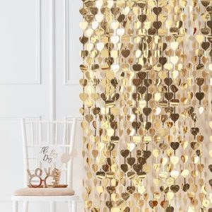 Cortina en color dorado con corazones.Esta cortina permite crear divertidos espacios y darles un toque festivo.Se puede poner de fondo para crear un photocall.